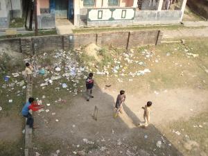 Malda - boys playing cricket among the rubbish