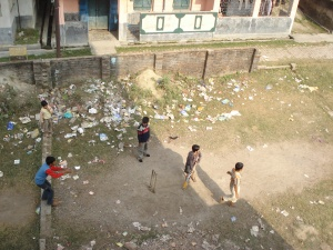 Malda - boys playing cricket among the rubbish